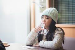 Стекло азиатской девушки выпивая воды в ресторане Стоковое Изображение RF