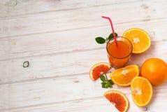 Стекло апельсинового сока и группа в составе апельсины на yabl белой доски Стоковые Фотографии RF