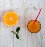 Стекло апельсинового сока и группа в составе апельсины на yabl белой доски Стоковая Фотография RF