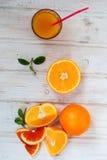 Стекло апельсинового сока и группа в составе апельсины на yabl белой доски Стоковые Изображения RF