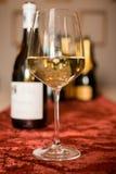 Стекло белого вина на бархате с бутылками вина в Backgrouind Стоковые Фото