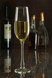 Стекло белого вина на таблице зеркала бутылки в баре на предпосылке Стоковое фото RF