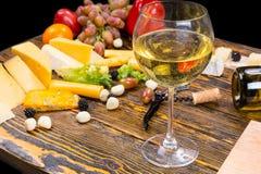 Стекло белого вина на таблице с сыром и плодоовощ Стоковые Фото