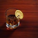Стекло вискиа Highball с льдом и лимоном на деревянной предпосылке Стоковые Изображения