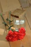 Стекло водочки и красных гвоздик на деревянном столе Стоковые Изображения