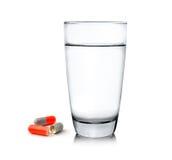 Стекло воды и пилюлек на белой предпосылке Стоковые Изображения