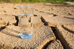 Стекло воды на иссушанной почве i стоковое изображение rf