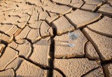 Стекло воды на иссушанной почве v стоковые фотографии rf
