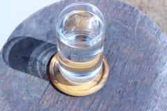 Стекло воды на старых деревянных стульях Стоковое фото RF