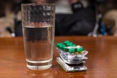 Стекло воды на таблице около стога пилюлек Стоковая Фотография RF