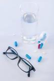 Стекло воды, пилюльки и eyeglasses на поверхности Стоковое Фото