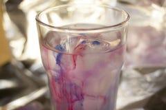 Стекло воды с красками стоковое изображение rf