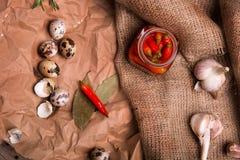 Стекло горячих красных перцев, яичек триперсток, розмаринового масла и чеснока на скомканной бумажной и деревенской ткани ингриди Стоковое Изображение
