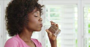Стекло женщины выпивая воды и усмехаться сток-видео
