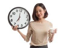 Стекло здоровой азиатской женщины выпивая часов владением молока Стоковое фото RF