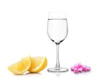 Стекло лимона воды и пилюлек изолированных на белой предпосылке Стоковое Изображение RF