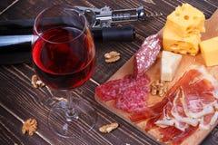 Стекло и бутылка вина, сыра и ветчины на деревянной предпосылке стоковые фотографии rf