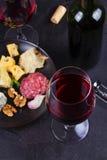 Стекло и бутылка красного вина, сыра, хлеба, чеснока, гаек, салями на серой каменной предпосылке текстуры Стоковые Изображения