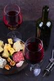 Стекло и бутылка красного вина, сыра, хлеба, чеснока, гаек, салями на серой каменной предпосылке текстуры Стоковое Изображение RF