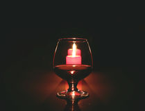 Стекло и свеча коньяка фото состава рождества на черной предпосылке Стоковое фото RF