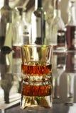 Стекло коньяка, рябиновки или whiscy на таблице зеркала бутылки в баре на предпосылке Стоковая Фотография RF
