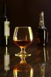 Стекло коньяка, рябиновки или whiscy на черной таблице зеркала бутылки в баре на предпосылке Стоковые Фотографии RF