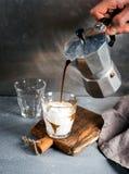 Стекло кофе с мороженым на деревенской деревянной доске Питье полито от стального бака Moka итальянки, который держит рука челове Стоковые Фото