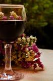 Стекло красного вина и цветков Стоковые Изображения