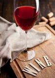 Стекло красного вина на деревянной доске с письмами и пробочками Стоковое фото RF
