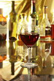 Стекло красного вина на таблице зеркала бутылки в баре на предпосылке Стоковые Фотографии RF