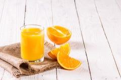 Стекло кусков сока и апельсина на таблице Стоковое Изображение RF