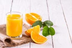 Стекло кусков сока и апельсина на таблице Стоковая Фотография RF