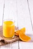 Стекло кусков сока и апельсина на таблице Стоковые Фотографии RF