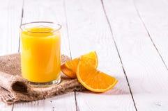 Стекло кусков сока и апельсина на таблице Стоковое Изображение
