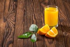 Стекло кусков сока и апельсина на таблице Стоковые Изображения RF