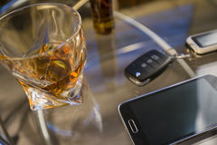Стекло ключа алкогольного напитка и автомобиля, на таблице, светлая предпосылка Стоковые Фотографии RF