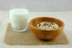 Стекло молока и деревянного шара с овсом шелушится на ткани мешковины Стоковая Фотография RF