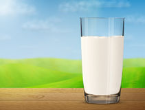 Стекло молока на деревянном столе на предпосылке запачканного ландшафта Стоковые Изображения