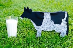 Стекло молока с классн классным молочной коровы деревянным на траве Стоковая Фотография