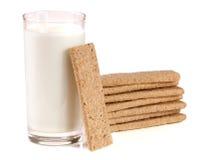 Стекло молока с стогом crispbreads зерна изолированных на белой предпосылке Стоковая Фотография