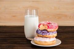 Стекло молока с donuts на плите на деревянной предпосылке Стоковые Фото