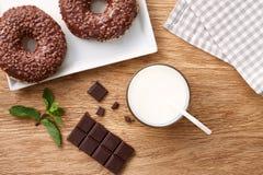 Стекло молока с donuts шоколада на деревянном столе Стоковые Изображения RF