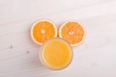 Стекло оранжевого свежего сока на светлой таблице и ушах апельсина покрывает Стоковые Изображения