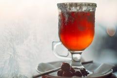 Стекло очень вкусного потока glintwein вишни на винтажной предпосылке зимы Стоковые Фото
