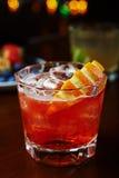 Стекло очень вкусного спиртного коктеиля или лимонада вискиа с льдом и кусок апельсина на таблице в баре или ресторан с de Стоковое Изображение
