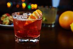 Стекло очень вкусного спиртного коктеиля или лимонада вискиа с льдом и кусок апельсина на таблице в баре или ресторан с de Стоковое Изображение RF