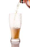 стекло пива будучи политым от бутылки изолированной на белой предпосылке Стоковые Фотографии RF