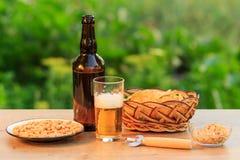 Стекло пива и бутылки пива на деревянном столе с хиом картошки Стоковое фото RF