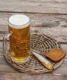 Стекло пива и копченых рыб на деревянном столе Стоковое Изображение RF