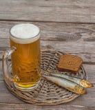 Стекло пива и копченых рыб на деревянном столе Стоковые Фото